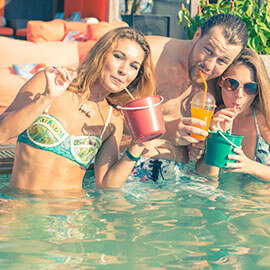 Young adults lounging in a pool with drinks