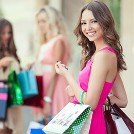 A woman in a pink dress with many shopping bags