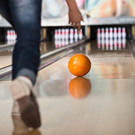 A bowling ball being rolled down a bowling alley