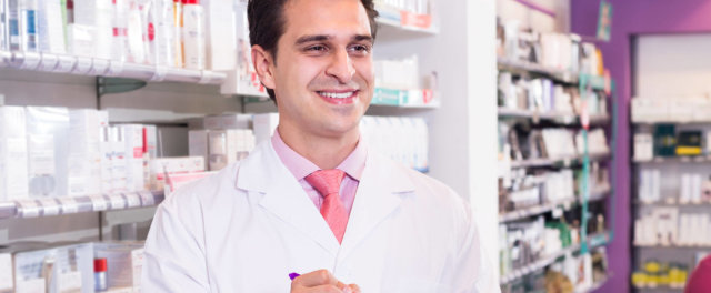 A man in a lab coat in a pharmacy