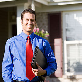 A man standing in front of a house wearing a blue dress shirt and a red tie