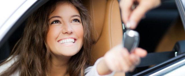 A woman in a car receiving a set of keys