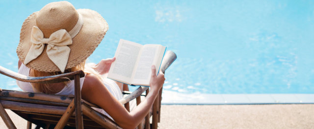 A woman in a hat reading a book poolside