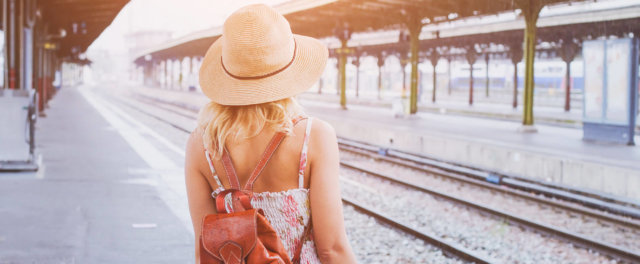 A woman with a backpack waiting at a train station