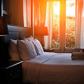 Sun shining in though a window on a made bed at a hotel