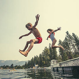 Children jumping into a lake