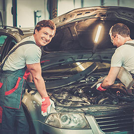 Two mechanics working under the hood of a car