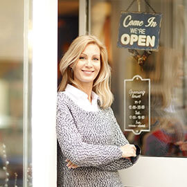 A business owner at the front door of her open establishment