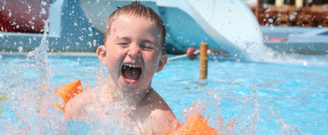 A boy splashing around in a pool