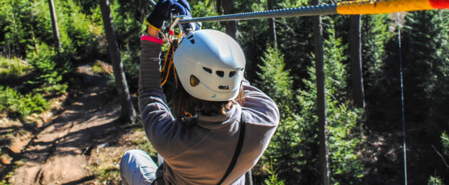Person in helmet starting down a zipline