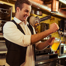 A man pouring a glass of beer from a tapper