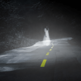 A ghostly figure down a dark road